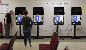 In this Thursday, Oct. 19, 2017, file photo, Kelly Monroe, investigator with the Georgia Secretary of State office, left, takes a look at a new voting machine that produces a paper record being tested at a polling site in Conyers, Ga. (AP Photo/David Goldman, File)