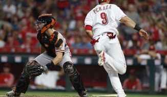 Cincinnati Reds' Jose Peraza (9) scores as San Francisco Giants catcher Buster Posey, left, looks for the throw during the fifth inning of a baseball game Saturday, Aug. 18, 2018, in Cincinnati. (AP Photo/Gary Landers)