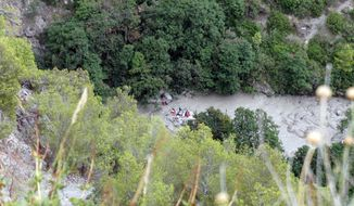 Rescuers work at the Raganello Gorge in Civita, Italy, Monday, Aug. 20, 2018.  At least eight people were killed when heavy rain flooded a gorge filled with hikers in the southern region of Calabria, Italy's civil protection agency said. The dead included four men and four women. The head of civil protection in Calabria, Carlo Tansi, told Sky TG24 that 12, including a 10-year-old boy, were brought to safety in the flash flood in the Raganello Gorge, a popular hiking spot. The boy was among six people who were injured. (Francesco Capitaneo/ANSA via AP)