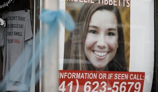 A poster for missing University of Iowa student Mollie Tibbetts hangs in the window of a local business, Tuesday, Aug. 21, 2018, in Brooklyn, Iowa. Tibbetts was reported missing from her hometown in the eastern Iowa city of Brooklyn in July 2018. (AP Photo/Charlie Neibergall)