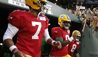 FILE - In this Aug. 4, 2018 file photo Green Bay Packers quarterbacks Brett Hundley (7) and DeShone Kizer (9) run onto Lambeau Field for the NFL football team's Family Night practice in Green Bay, Wis. Quarterback Tim Boyle is at right. The last two preseason games may determine whether Hundley or Kizer wins the backup quarterback job for the Green Bay Packers. It's a unique position because in a best-case scenario for the Packers, the backup wouldn't play meaningful snaps in the regular season since that would mean that starter Aaron Rodgers was healthy. The Packers experienced the worst-case scenario last year, when they stumbled to 7-9 and missed the playoffs when Rodgers got hurt. (AP Photo/Mike Roemer, file)