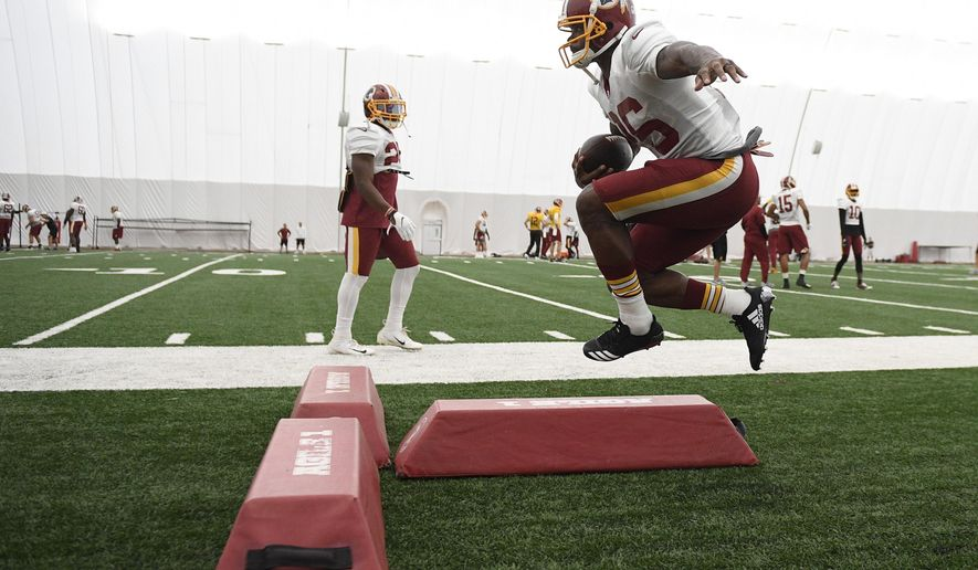 Washington Redskins running back Adrian Peterson runs with the ball during an NFL football team practice, Tuesday, Aug. 21, 2018, in Ashburn, Va. (AP Photo/Nick Wass)
