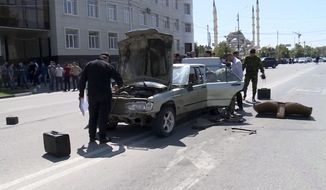 In this video grab provided by the RU-RTR Russian television, Investigators inspect a car that was allegedly used to attack police in the regional capital, Grozny, Russia, Monday, Aug. 20, 2018. Islamic militants launched a series of attacks Monday in Russia's southern province of Chechnya, leaving five young militants dead and several police officers wounded, officials said. (RU-RTR Russian Television via AP)
