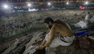 A Muslim hajji pilgrim washes, performing ablution before offering early morning prayers at Jabal Al Rahma holy mountain, or the mountain of forgiveness, at Arafat for the annual hajj pilgrimage, outside the holy city of Mecca, Saudi Arabia, Monday, Aug. 20, 2018. More than 2 million Muslims have begun the annual hajj pilgrimage, one of the five pillars of Islam which is required of all able-bodied Muslims once in their lifetime.(AP Photo/Dar Yasin)
