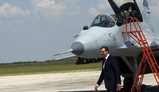 Serbian President Aleksandar Vucic walks by a MiG-29 jet fighter on the tarmac at Batajnica, military airport near Belgrade, Serbia, Tuesday, Aug. 21, 2018. Serbia's air force has taken the delivery of two Russian MiG-29 fighter jets, part of an arms purchase that has the potential to heighten tensions in the Balkans and increase Moscow's influence in the region. (AP Photo/Darko Vojinovic)