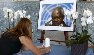 An UN staff member puts a candle in front of portrait of former United Nations Secretary General Kofi Annan prior to a ceremony of UN staff to pay tribute to Kofi Annan, at the 'Salle des Pas Perdu' in the European headquarters of the United Nations in Geneva, Switzerland, Monday, Aug. 20, 2018. Annan died on Aug. 18 2018 at the age of 80 years. (Salvatore Di Nolfi/Keystone via AP)
