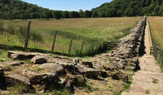 In this July 3, 2018 photo, a stretch of Hadrian's Wall cuts through the northern English countryside, near Birdoswald Fort, Cumbria. The wall was built by Roman soldiers, beginning in 122 AD, to control movement across the frontier and to protect their territory from warlike tribes. When finished it ran from coast to coast: a distance of 118 kilometers (73 miles). Large parts of it remain today. (AP Photo/Jerry Harmer)