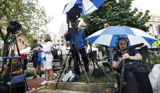 Television crews wait for news outside the trial of Paul Manafort, outside of federal court before Manafort, the longtime political operative who for months led Donald Trump's winning presidential campaign, was found guilty of eight financial crimes in the first trial victory of the special counsel investigation into the president's associates in Alexandria, Va., Tuesday, Aug. 21, 2018. (AP Photo/Jacquelyn Martin)