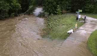 Onlookers get a close view of Pheasant Branch Creek, below the bridge on Parmenter Street, as the water covers the nearby bike path after Monday's record rainfall hit the area causing flooding, in Middleton, Wis., Tuesday, Aug. 21, 2018. (Amber Arnold/Wisconsin State Journal via AP)