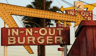 In-N-Out Burger signs, two in the foreground from the fast food chain's original location, and one in the background at a new location across the Interstate 10 freeway, fill the skyline in Baldwin Park, California, June 8, 2010. (AP Photo/Adam Lau) ** FILE **