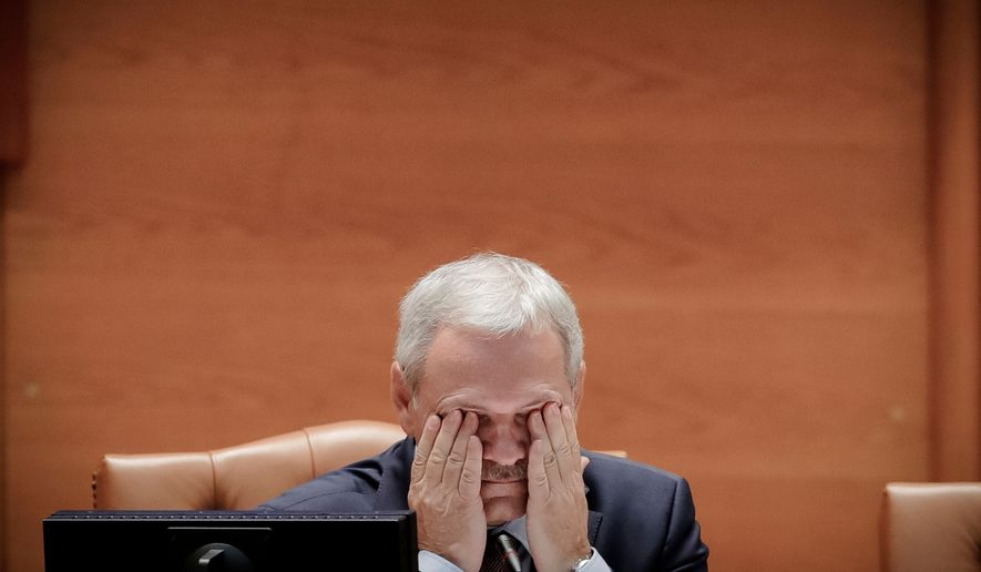 FILE- In this Wednesday, June 21, 2017, file photo, the head of the Ruling Social Democratic Party, Liviu Dragnea wipes his eyes at the Romanian parliament in Bucharest, Romania. Claims by the leader of Romania's ruling party that he was the target of a failed assassination attempt have sparked wide debate in the country after Liviu Dragnea told a television station late Tuesday, Aug. 21, that 4 foreigners had come to Bucharest for the April 2017 assignment, but had been thwarted.(AP Photo/Vadim Ghirda, File)