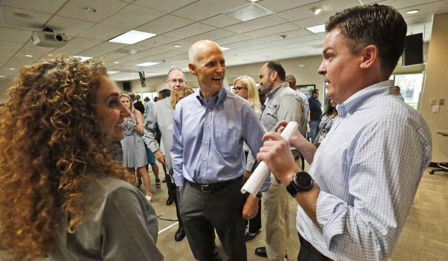 Florida Gov. Rick Scott, center, chats with Secretary of the Florida Department of Transportation (FDOT) Mike Dew, right, and Stacy Miller, left, director of transportation development, after a news conference at the FDOT District Four Office, Wednesday, Aug. 22, 2018, in Fort Lauderdale, Fla. Scott spoke about the SW 10th Street Connector. Scott is challenging three-term Democratic U.S. Sen. Bill Nelson. (AP Photo/Wilfredo Lee) ** FILE **