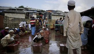 Rohingya refugees perform ablution before offering Eid al Adha prayers at Kutupalong refugee camp, Bangladesh, Wednesday, Aug. 22, 2018. Hundreds of thousands of Rohingya refugees in sprawling Bangladeshi camps are celebrating Eid al-Adha Wednesday amid festivity and confusion over whether they would ever be able to go back to Myanmar they fled amid violence and a massive crackdown. (AP Photo/Altaf Qadri)