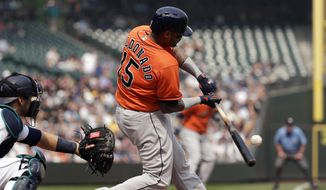 Houston Astros' Martin Maldonado singles in a run as Seattle Mariners catcher Mike Zunino looks on in the second inning of a baseball game Wednesday, Aug. 22, 2018, in Seattle. (AP Photo/Elaine Thompson)