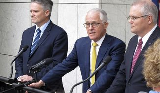 Australia's Finance Minister Mathias Cormann, left, Prime Minister Malcolm Turnbull, center, and Treasurer Scott Morrison address media at Parliament House in Canberra, Australia, Wednesday, Aug. 22, 2018. The two ministers declared their support for Turnbull remaining prime minister as another lawmaker prepares a leadership challenge. (AP Photo/Rod McGuirk)