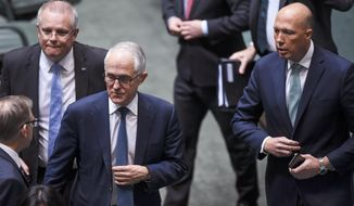 Australian Federal Treasurer Scott Morrison, second left, Prime Minister Malcolm Turnbull, center, and former Home Affairs Minister Peter Dutton, right, leave the chamber at Parliament House in Canberra, Thursday, Aug. 23, 2018, after a vote to refer former Dutton to the High Court to determine whether he is eligible to be a lawmaker, Thursday, Aug. 23, 2018. Three senior Cabinet ministers have told Turnbull he has lost his government's support and must hold an internal ballot to elect a new leader quickly. (Lukas Coch/AAP Image via AP)