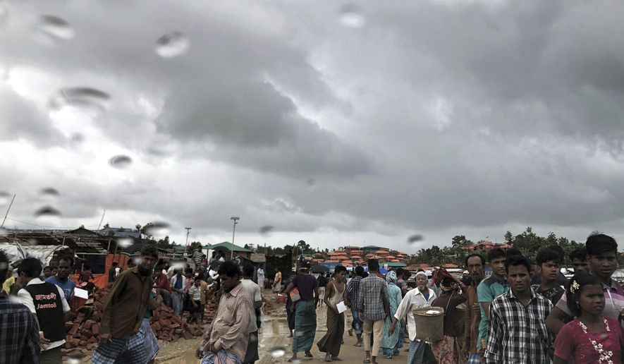 In this Tuesday, June 26, 2018, photo, Rohingya refugees walk on a muddy road in the rain through Jamtoli refugee camp in Bangladesh. For the hundreds of thousands of Rohingya children living in Bangladesh's refugee camps, dangers lurk everywhere: from malnutrition and disease to human traffickers to flooding and landslides. (AP Photo/Wong Maye-E)