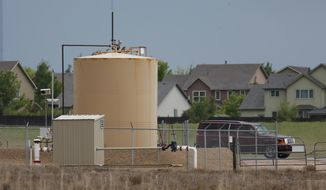 FILE - In this May 27, 2016, file photo, tanks sit near a housing development off state highway 119 near Firestone, Colo. The proximity of homes and schools to oil and gas facilities is often a contentious issue in Colorado and has become an issue in the November election. Gubernatorial candidates Walker Stapleton, a Republican, and Jared Polis, a Democrat, outlined their energy policies on Wednesday, Aug. 22, 2018, at a meeting of the Colorado Oil and Gas Association in Denver. (AP Photo/David Zalubowski,File)