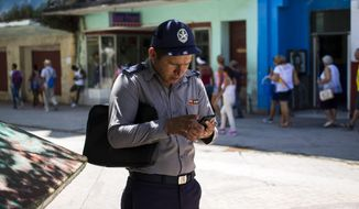 A policeman gets connected to the internet using his phone in Havana, Cuba, Wednesday, Aug. 22, 2018. The state telecommunications company of Cuba launched on Wednesday the latest, and most extensive, of a recent series of test runs of a mobile network that would give ordinary citizens greater access to the internet than has existed before on the island. (AP Photo/Desmond Boylan)