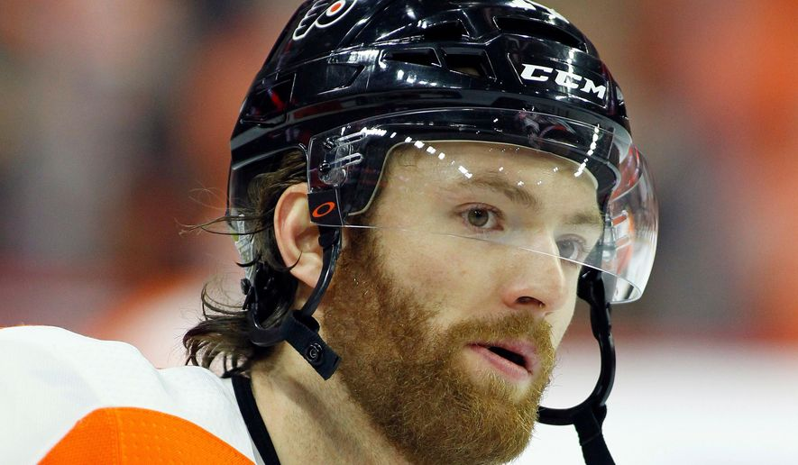 FILE - This is an April 22, 2018, file photo showing Philadelphia Flyers' Sean Couturier during warm-ups before the start of an NHL hockey game in Philadelphia. Couturier is out four weeks after suffering a knee injury for the second time in five months.  General manager Ron Hextall provided the update Wednesday, Aug. 22, 2018, saying Couturier was injured Aug. 10 in an exhibition game. (AP Photo/Tom Mihalek, File)