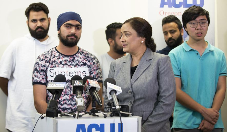 Asylum seeker Lovepreet Singh, who had been detained at the federal prison in Sheridan, Oregon, speaks along with interpreter Navneet Kaur, right, about his experiences in prison and relief at being released at the ACLU office in Portland on Wednesday, Aug. 22, 2018.  (Dave Killen/The Oregonian via AP)