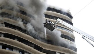 Smoke emits as fire brigade personnel try to douse a fire on the 12th floor of Crystal Tower, a residential  building in Mumbai, India, Wednesday, Aug.22, 2018. Four people were killed and 12 others were injured according to officials. (AP Photo/Emmanual Yogini)