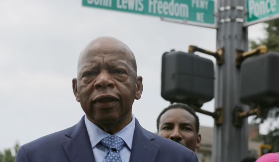 U.S. Rep. John Lewis stands in front of John Lewis Freedom Parkway moments after its new name was unveiled in Atlanta, Wednesday, Aug. 22, 2018. Atlanta is honoring Lewis by renaming a street after the civil rights icon. (AP Photos/Brinley Hineman)