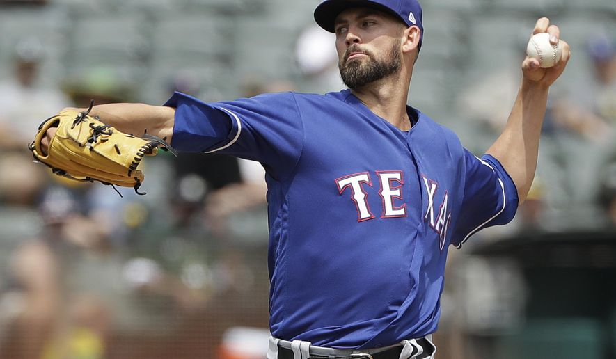 Texas Rangers pitcher Mike Minor throws against the Oakland Athletics during the first inning of a baseball game in Oakland, Calif., Wednesday, Aug. 22, 2018. (AP Photo/Jeff Chiu)
