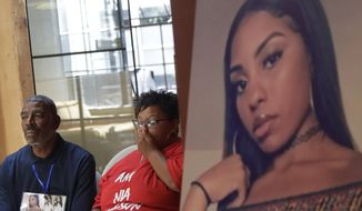 """FILE - In this Aug. 17, 2018, file photo, a photo of victim Nia Wilson, right, is displayed at a news conference as her father Ansar El Muhammad, left, and her mother Alicia Grayson listen during a news conference in San Francisco. Prosecutors have special circumstances charges against John Cowell who was arrested in the killing of Wilson at a train station in Northern California. Alameda County District Attorney's Office on Wednesday, Aug. 22, 2018, added the special circumstances enhancement of """"lying in wait"""" to Cowell's complaint, allegations that could make him eligible for the death penalty. (AP Photo/Jeff Chiu, File)"""