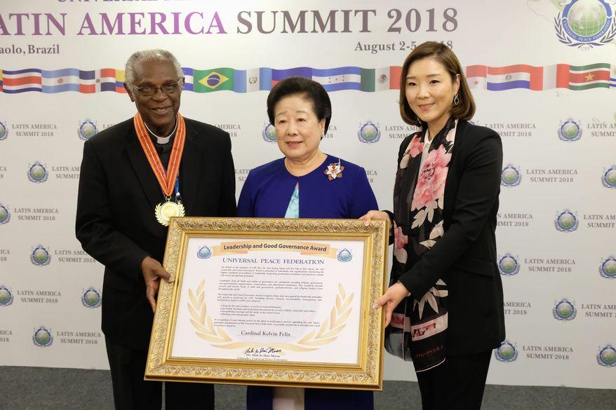 Roman Catholic Cardinal Kelvin Felix receives leadership award from Mother Moon and Dr. Sun Jin Moon, International President of FFWPU. (PHOTO CREDIT: HSA-UWC)