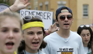 David Hogg, center right, a survivor of the school shooting at Marjory Stoneman Douglas High School, in Parkland, Fla., walks in a planned 50-mile march, Thursday, Aug. 23, 2018, in Worcester, Mass. The march, held to call for gun law reforms, began Thursday, in Worcester, and is scheduled to end Sunday, Aug. 26, 2018, in Springfield, Mass., at the headquarters of gun manufacturer Smith & Wesson. (AP Photo/Steven Senne)