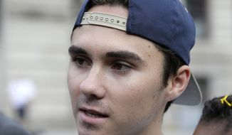 David Hogg, a survivor of the school shooting at Marjory Stoneman Douglas High School, in Parkland, Florida, speaks with reporters before walking in a planned 50-mile march, Thursday, Aug. 23, 2018, in Worcester, Mass. The march, held to call for gun law reforms, began Thursday, in Worcester, and is scheduled to end Sunday, Aug. 26, 2018, in Springfield, Mass., at the headquarters of gun manufacturer Smith & Wesson. (AP Photo/Steven Senne)