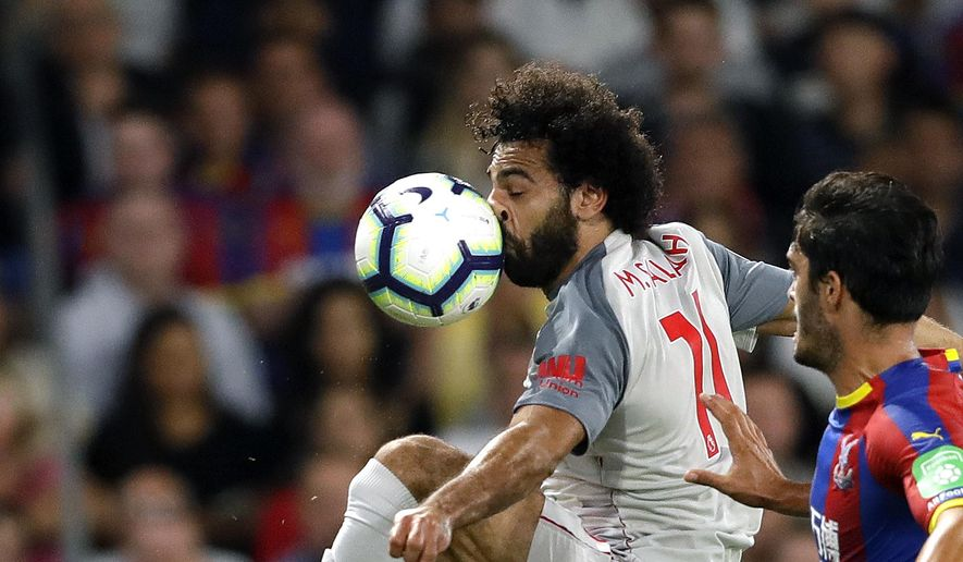 Liverpool's Mohamed Salah, left, duels for the ball with Crystal Palace's James Tomkins during the English Premier League soccer match between Crystal Palace and Liverpool at Selhurst Park stadium in London, Monday, Aug. 20, 2018. (AP Photo/Kirsty Wigglesworth)