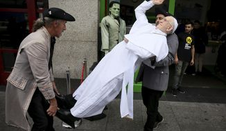 A newly unveiled wax work of Pope Francis is carried at the National Wax Museum Plus where they also unveiled a newly refurbished original 1979 Pope Mobile ahead of Pope Francis' visit to Ireland, in Dublin, Thursday Aug. 23, 2018. (Brian Lawless/ PA via AP)