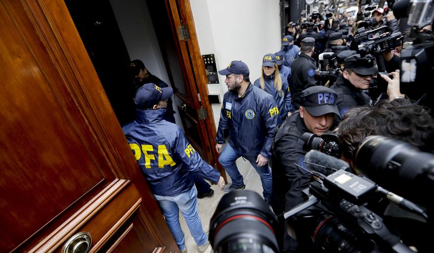 Police enter the home of Senator and Former President Cristina Fernandez, in Buenos Aires, Argentina, Thursday, Aug. 23, 2018. Argentine Senators authorized a judge's request to carry out search warrants on properties owned by the former President as part of a case investigating widespread corruption. (AP Photo/Natacha Pisarenko)