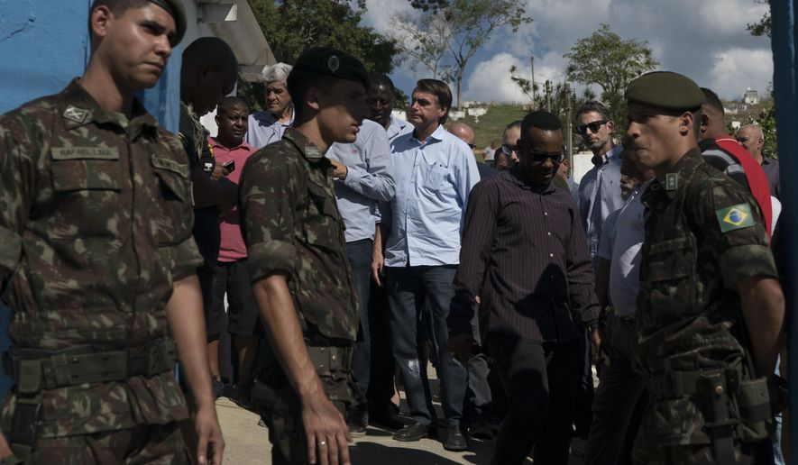 National Social Liberal Party presidential candidate Jair Bolsonaro, center, leaves the cemetery after attending the burial of soldier Fabiano de Oliveira dos Santos in Japeri, Brazil, Tuesday, Aug. 21, 2018. At least 11 suspects and two soldiers died during shootouts with military personnel and police in greater Rio de Janeiro on Monday as violence erupted in several areas of the city that hosted the Summer Olympics two years ago. (AP Photo/Leo Correa)