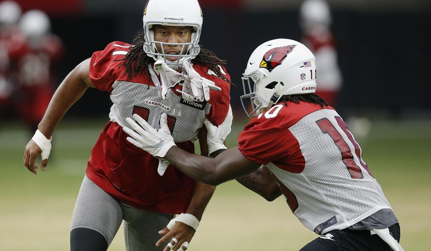 Arizona Cardinals wide receiver Larry Fitzgerald (11) tries to shed a block from wide receiver Chad Williams, right, during an NFL football practice Monday, Aug. 13, 2018, in Glendale, Ariz. (AP Photo/Ross D. Franklin)