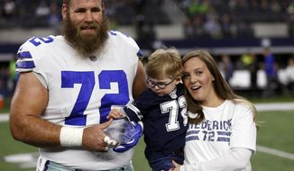 FILE - In this Dec. 24, 2017, file photo, Dallas Cowboys center Travis Frederick (72), and his wife Kaylee, right, pose for a photo as their son Oliver, reaches out to the NFL Man of the Year team nominee award presented to Frederick before an NFL football game against the Seattle Seahawks, in Arlington, Texas. Frederick's revelation that he is battling a rare neurological disorder will reverberate on and off the field for the Dallas Cowboys. They're likely to begin the season without their stalwart at center, and without knowing what will happen with their teammate's recovery. (AP Photo/Ron Jenkins, File)