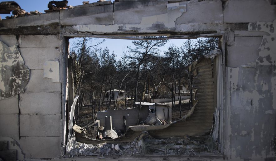 Burned houses are seen through a gutted window frame one month after a deadly wildfire tore through holiday homes near Athens, on at the seaside area of Mati, on Wednesday, Aug. 22, 2018. Authorities are still investigating the cause of the fire that killed more than 90 people at seaside resorts east of Athens, destroyed or seriously damaged several thousand homes, torched hundreds of cars, and touched off a political spat that forced country's minister of public order to resign. (AP Photo/Petros Giannakouris)