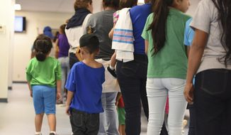 In this Aug. 9, 2018, photo, provided by U.S. Immigration and Customs Enforcement, mothers and their children stand in line at South Texas Family Residential Center in Dilley, Texas. A complaint expected to be filed Thursday, Aug. 23 with the Department of Homeland Security alleges that immigration authorities coerced dozens of parents separated from their children at the border to sign documents they didn't understand. In some of those cases, parents gave away rights to be reunited with their kids. The complaint will be filed by the American Immigration Lawyers Association and the American Immigration Council. (Charles Reed/U.S. Immigration and Customs Enforcement via AP) **FILE**