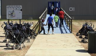 In this Aug. 9, 2018, photo, provided by U.S. Immigration and Customs Enforcement, immigrants walk into a building at South Texas Family Residential Center in Dilley, Texas. A complaint expected to be filed Thursday, Aug. 23 with the Department of Homeland Security alleges that immigration authorities coerced dozens of parents separated from their children at the border to sign documents they didn't understand. In some of those cases, parents gave away rights to be reunited with their kids. The complaint will be filed by the American Immigration Lawyers Association and the American Immigration Council. (Charles Reed/U.S. Immigration and Customs Enforcement via AP) **FILE**