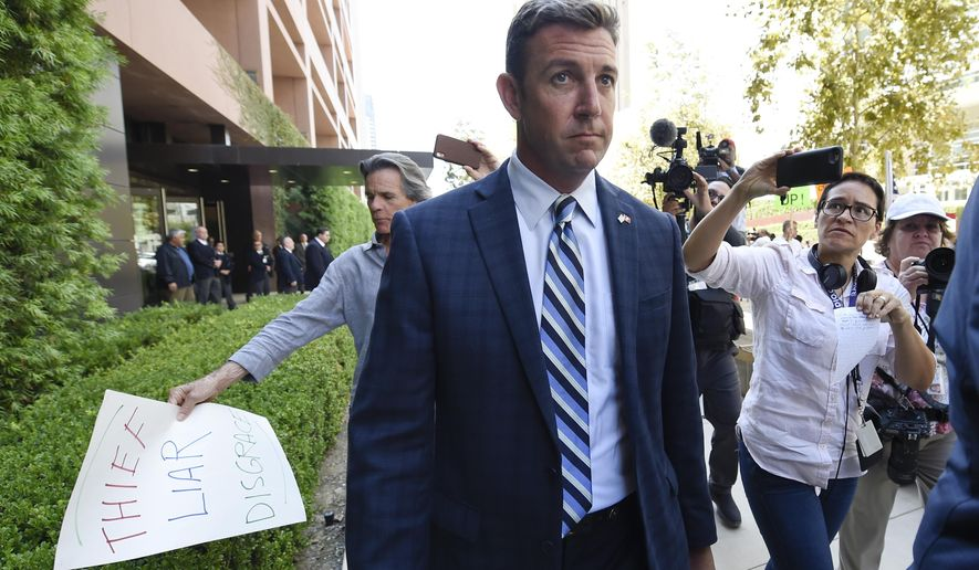 U.S. Rep. Duncan Hunter, center, leaves an arraignment hearing as a protester carries a sign, left, Thursday, Aug. 23, 2018, in San Diego. Hunter and his wife Margaret pleaded not guilty Thursday to charges they illegally used his campaign account for personal expenses. (AP Photo/Denis Poroy)