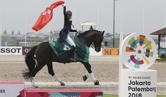 Hong Kong's Jacqueline Wing Ying Siu celebrates after winning gold medal during dressage individual intermediate I freestyle equestrian at the 18th Asian Games in Jakarta, Indonesia, Thursday, Aug. 23, 2018. (AP Photo/Achmad Ibrahim)