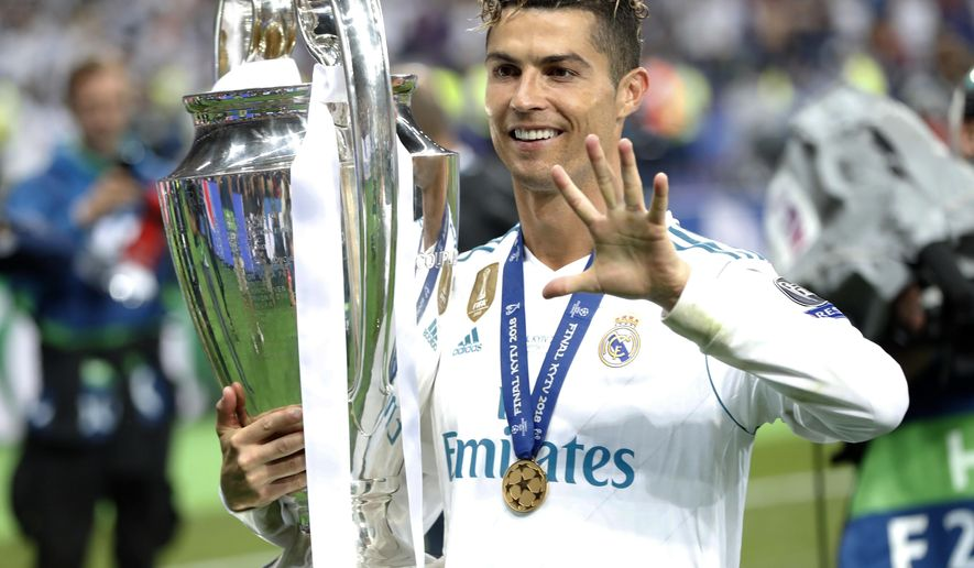 "FILE - In this Saturday, May 26, 2018 file photo Real Madrid's Cristiano Ronaldo celebrates with the trophy after winning the Champions League Final soccer match between Real Madrid and Liverpool at the Olimpiyskiy Stadium in Kiev, Ukraine. Cristiano Ronaldo says it was his ""destiny"" to join Juventus as he tries to become only the second player to win the Champions League with three different clubs. Ronaldo moved from Real Madrid to Juventus in a Serie A record 112 million euro (then $131.5 million) deal. (AP Photo/Pavel Golovkin)"