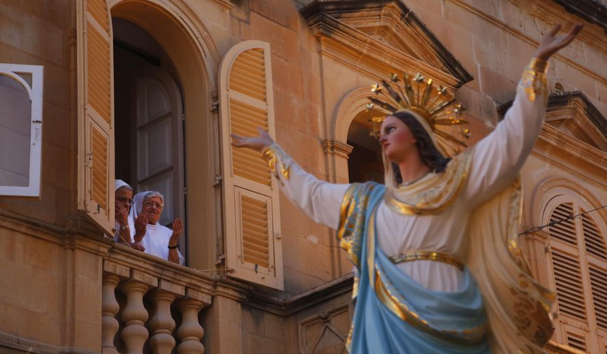 In this file photo taken on Wednesday, Aug. 15, 2018, nuns offer a prayer as the statue of the Virgin Mary being carried through the streets of Rabat on the island of Gozo in the Maltese archipelago, during the feast day of the Assumption of Mary. (AP Photo/Niranjan Shrestha) ** FILE **