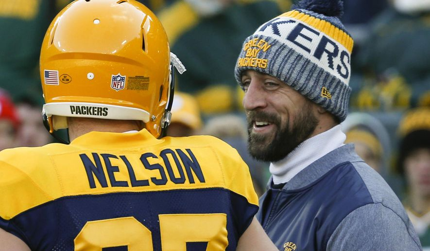 FILE - In this Nov. 19, 2017, file photo, Green Bay Packers' Aaron Rodgers talks to Jordy Nelson before an NFL football game against the Baltimore Ravens, in Green Bay, Wis. The departure of receiver Jordy Nelson has left Rodgers in need of a new partner to take part in one of his pregame routines. In the end zone before a game would be Rodgers and Nelson playing catch and spinning footballs on their fingertips. That won't happen Friday night now that Nelson is a Raider, though they remain good friends. (AP Photo/Mike Roemer)