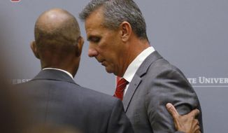 Ohio State University President Michael Drake offers words to football coach Urban Meyer, who leaves the stage following a news conference in Columbus, Ohio, Wednesday, Aug. 22, 2018. Ohio State suspended Meyer on Wednesday for three games for mishandling domestic violence accusations, punishing one of the sport's most prominent leaders for keeping an assistant on staff for several years after the coach's wife accused him of abuse. Athletic director Gene Smith was suspended from Aug. 31 through Sept. 16. (AP Photo/Paul Vernon)