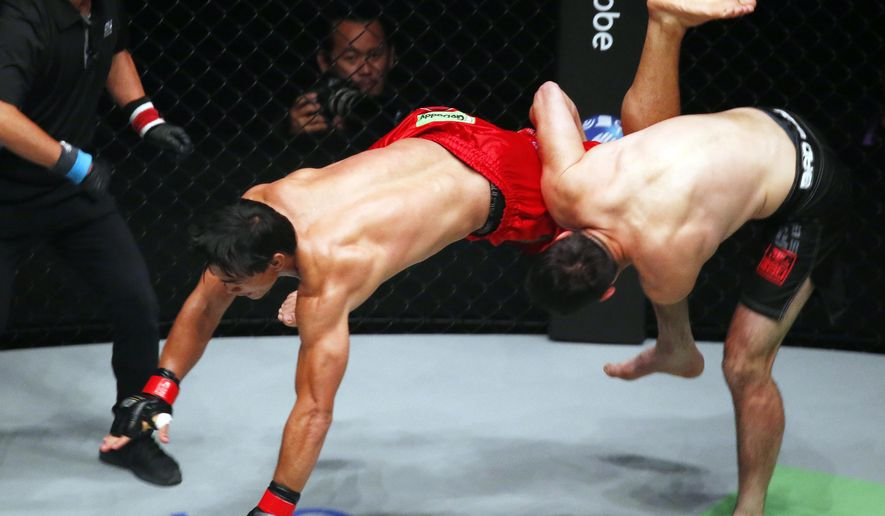 FILE - In this July 27, 2018, file photo, Aziz Pahrudinov, right, tries to take down former champion Eduard Folayang during their lightweight bout in the One Championship mixed martial arts event at the Mall of Asia Arena in Pasay city, Philippines. Folayang defeated Pahrudinov via unanimous decision. The One Championship has announced plans to hold its first show in Japan in March 2019. The Asia-based promotion also announced upcoming debut fight cards in South Korea and Vietnam during 2019 as it expands its reach across the continent. (AP Photo/Bullit Marquez, File)