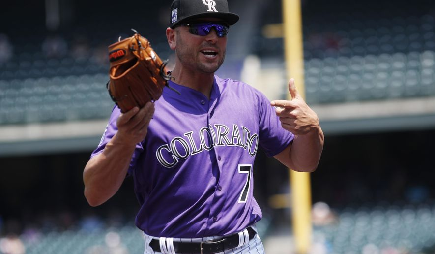 Colorado Rockies left fielder Matt Holliday points to his glove as he takes the field to face the San Diego Padres while signing autographs before a baseball game Thursday, Aug. 23, 2018, in Denver. (AP Photo/David Zalubowski)