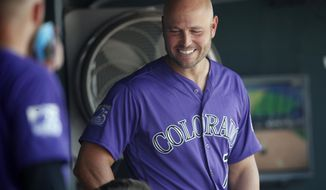 Colorado Rockies left fielder Matt Holliday laughs with teammates after watching a video tribute to mark his return to the Rockies before the first inning of a baseball game against the San Diego Padres Thursday, Aug. 23, 2018, in Denver. (AP Photo/David Zalubowski)